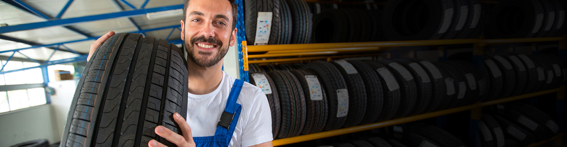 Smiling Mechanic Carrying Tire in Tire Store